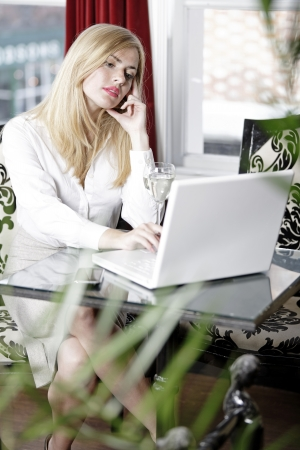Attractive woman working on her laptop catching up after a long day. Stock Photo - 16217690