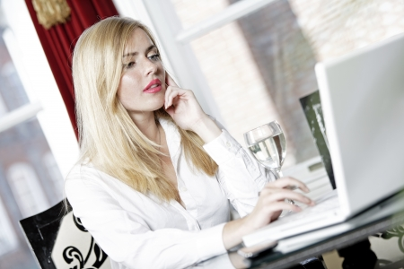Attractive woman working on her laptop catching up after a long day. Stock Photo - 16217709