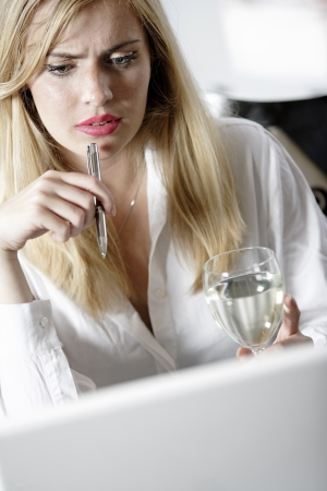 Attractive woman working on her laptop catching up after a long day. Stock Photo - 16217687