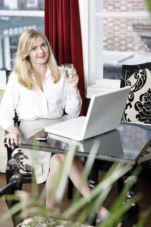 Attractive woman working on her laptop catching up after a long day. Stock Photo - 16217700