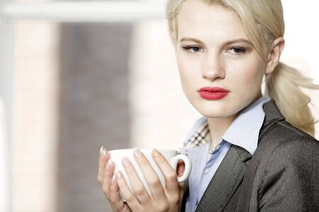 professional business woman drinking a mug of coffee at work. Stock Photo - 16217698