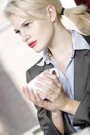 professional business woman drinking a mug of coffee at work. Stock Photo - 16217667