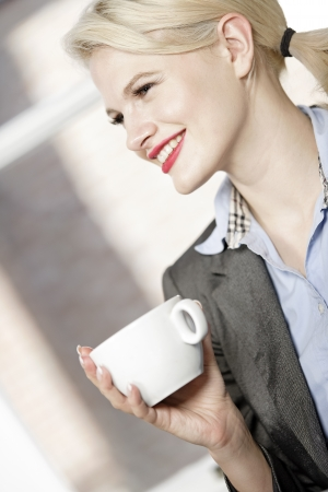 professional business woman drinking a mug of coffee at work. Stock Photo - 16217671
