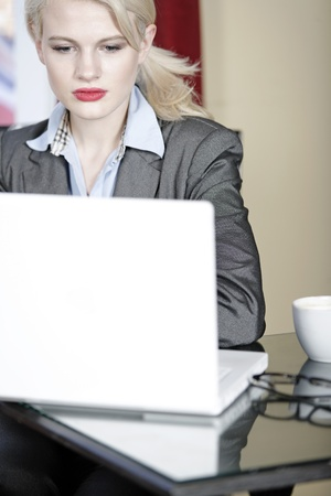 Attractive woman working on her laptop catching up after a long day. Stock Photo - 16217708