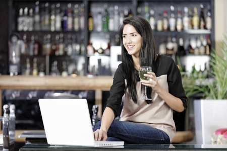 Beautiful young woman chatting with friends on her laptop while enjoying a glass of wine in a bar photo