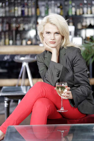 Attractive young woman enjoying a glass of white wine in a wine bar. photo