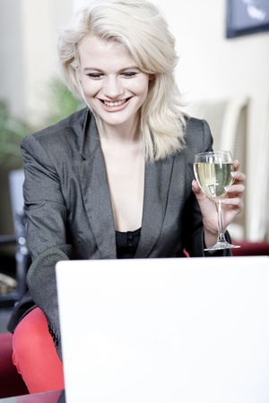 Beautiful young woman chatting with friends on her laptop while enjoying a glass of wine in a bar Stock Photo - 16217689