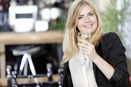 Attractive young woman enjoying a glass of white wine in a wine bar. Stock Photo - 16217675