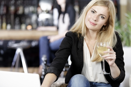 Beautiful young woman chatting with friends on her laptop while enjoying a glass of wine in a bar Stock Photo