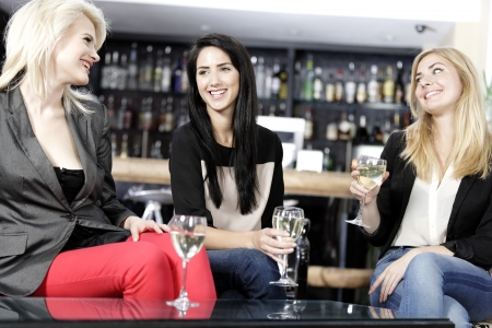 female friends enjoying a drink together at a wine bar. photo