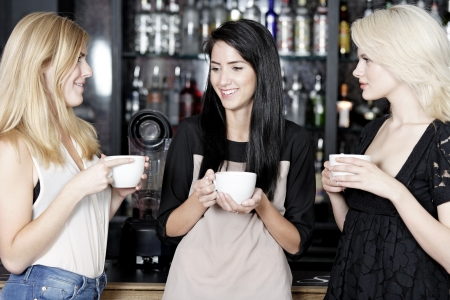 women talking: Beautiful young woman talking over coffee at a wine bar. Stock Photo