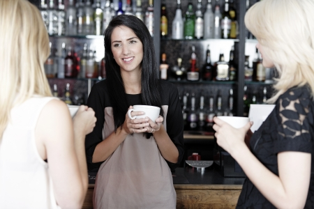 Beautiful young woman talking over coffee at a wine bar. Stock Photo - 16217662