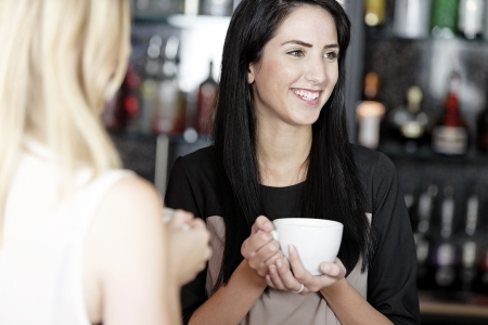 Beautiful young woman talking over coffee at a wine bar. Stock Photo