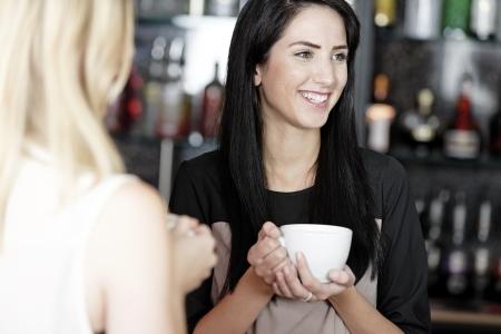 mujer tomando cafe: Joven y bella mujer hablando con un caf� en un bar de vinos. Foto de archivo