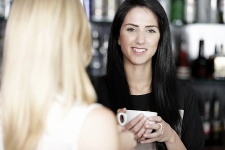 Beautiful young woman talking over coffee at a wine bar. photo