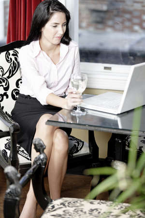 Attractive woman working on her laptop catching up after a long day. Stock Photo - 16217663