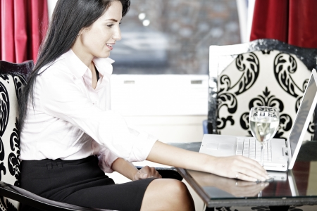 Attractive woman working on her laptop catching up after a long day. Stock Photo - 16217669