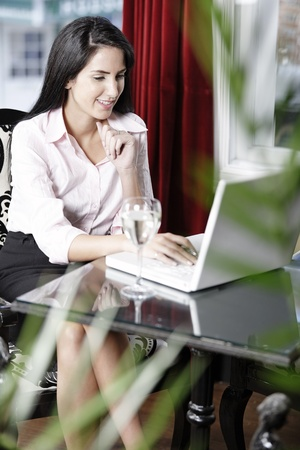Attractive woman working on her laptop catching up after a long day. Stock Photo - 16217664
