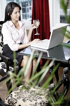 Attractive woman working on her laptop catching up after a long day. Stock Photo - 16217677