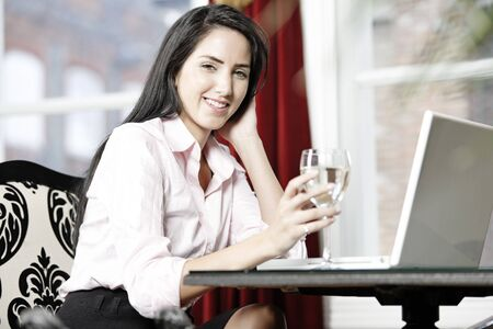Attractive woman working on her laptop catching up after a long day. Stock Photo - 16217713
