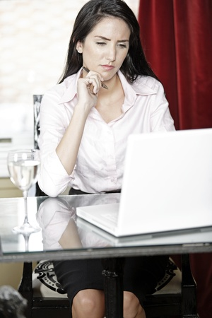 Attractive woman working on her laptop catching up after a long day. Stock Photo - 16217718