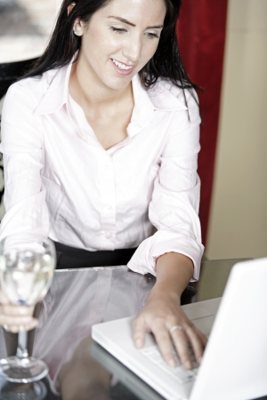Attractive woman working on her laptop catching up after a long day. Stock Photo - 16217706