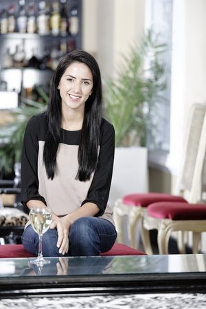 Attractive young woman enjoying a glass of white wine in a wine bar. Stock Photo - 16217699