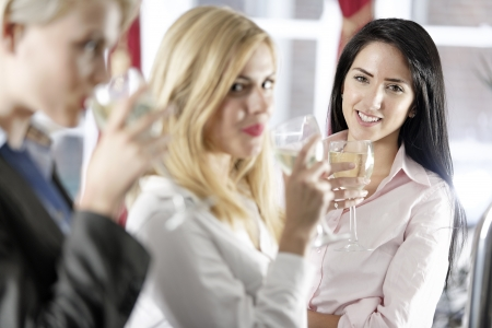 after work: Beautiful young women enjoying a glass of wine after work at a bar. Stock Photo