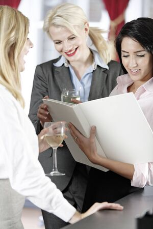 Three attractive work colleagues reading a wine list. Stock Photo - 18000767
