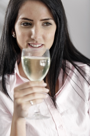 Young woman enjoying a glass of wine after work. Stock Photo - 18000758