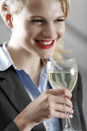 Young woman enjoying a glass of wine after work. Stock Photo - 18000748