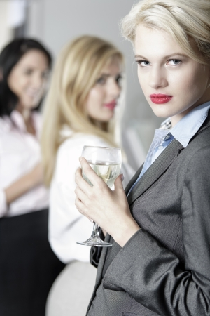 Beautiful young women enjoying a glass of wine after work at a bar. Stock Photo - 18000699