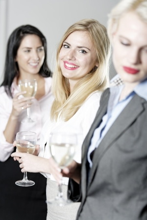Beautiful young women enjoying a glass of wine after work at a bar. Stock Photo - 18000759