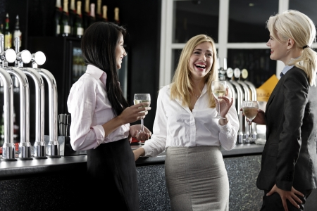 Beautiful young women enjoying a glass of wine after work at a bar. photo