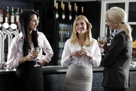 after to work: Hermosas mujeres j�venes disfrutando de una copa de vino despu�s del trabajo en un bar.