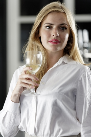 Young woman enjoying a glass of wine after work. Stock Photo - 18000736