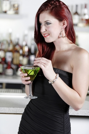 Beautiful young woman enjoying a cocktail drink at a bar Stock Photo - 18000738