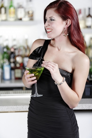 Beautiful young woman enjoying a cocktail drink at a bar Stock Photo - 18000742