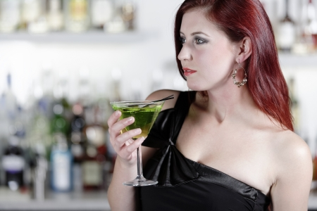 Beautiful young woman enjoying a cocktail drink at a bar Stock Photo - 18000750