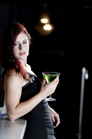 Beautiful young woman enjoying a cocktail drink at a bar Stock Photo - 18000766