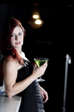 Beautiful young woman enjoying a cocktail drink at a bar Stock Photo - 18000766