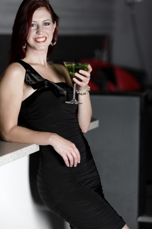 Beautiful young woman enjoying a cocktail drink at a bar Stock Photo - 18000732