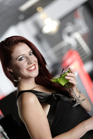 Beautiful young woman enjoying a cocktail drink at a bar Stock Photo - 18000749