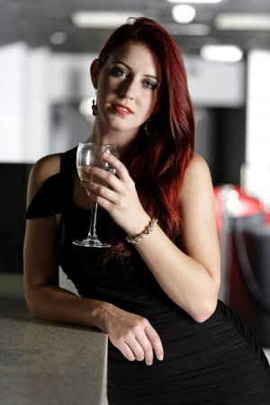 Beautiful young woman enjoying a glass of white wine at a bar. Stock Photo - 18000746