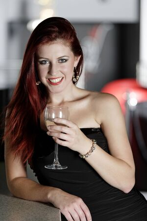 Beautiful young woman enjoying a glass of white wine at a bar. Stock Photo - 18000739