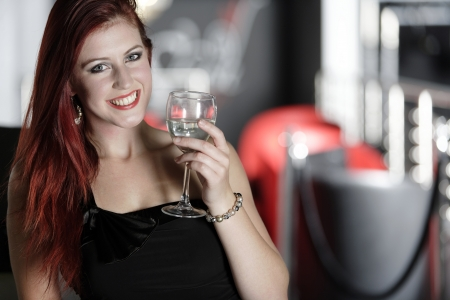 Beautiful young woman enjoying a glass of white wine at a bar. Stock Photo - 18000754