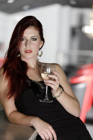 Beautiful young woman enjoying a glass of white wine at a bar. Stock Photo - 18000724