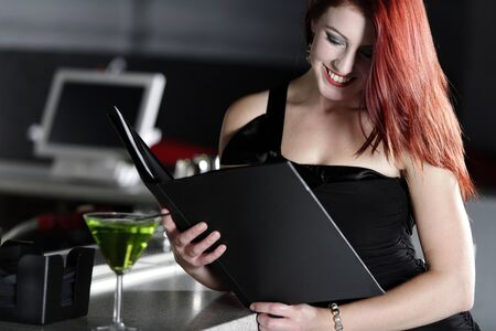 Attractive young woman reading from a wine list at the bar. Stock Photo - 18000737