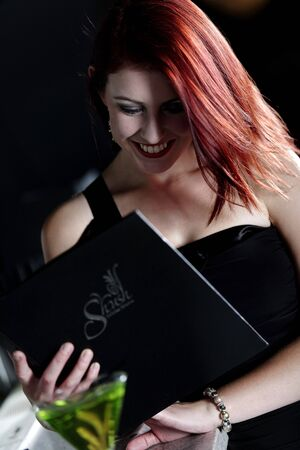 Attractive young woman reading from a wine list at the bar. Stock Photo - 18000707