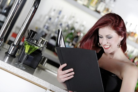 Attractive young woman reading from a wine list at the bar. Stock Photo - 18000735